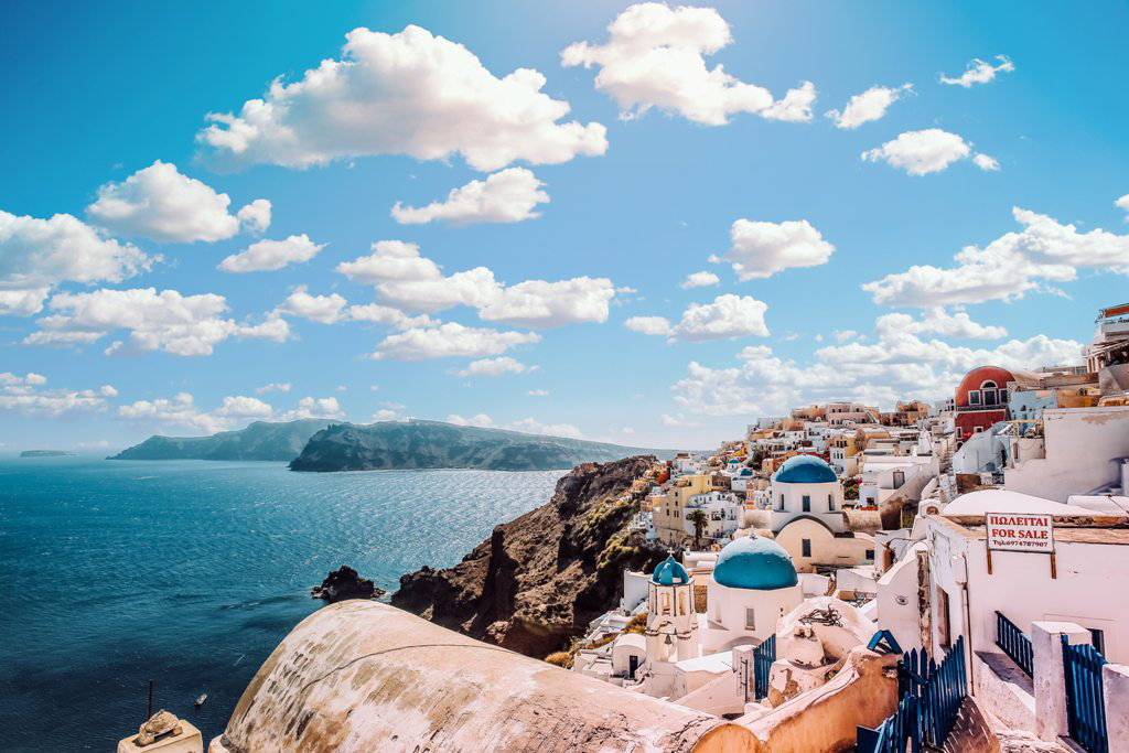 Travelling_to_Greece_-_white-concrete-house-near-body-of-water-under-white-and-blue-1285625.png